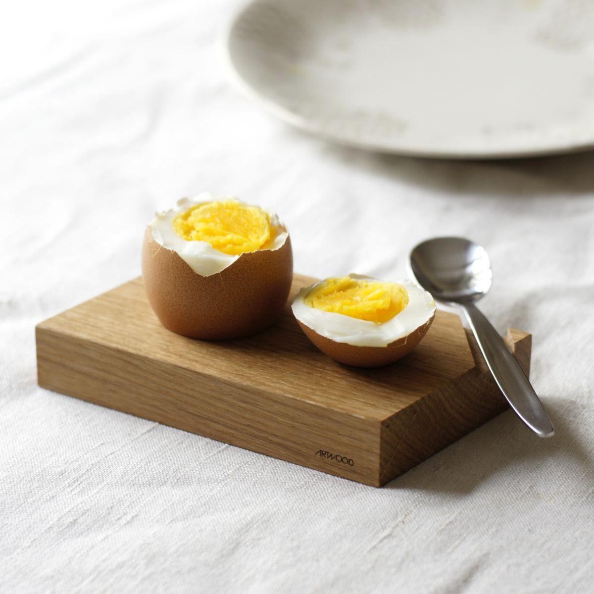 Eierbecher aus hellem Holz mit Löffel und Ablage für die Eierkuppe.